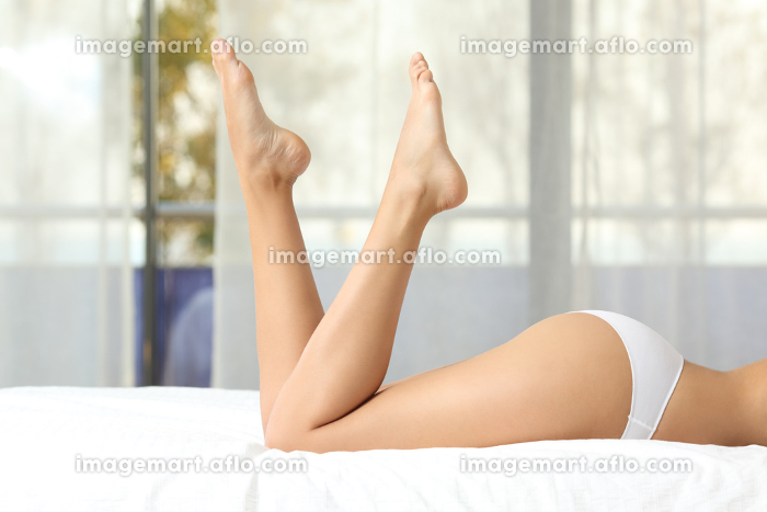 Perfect woman waxed legs on a bedの販売画像