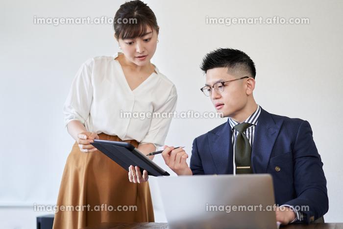 アジア人の先輩ビジネスマンに資料のチェックをお願いするビジネスウーマンの販売画像