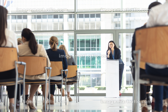 Front view of young Asian female executive doing speech in conference roomの販売画像
