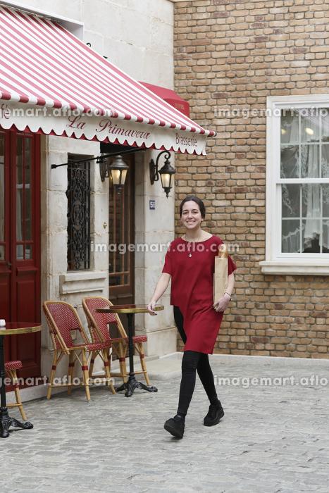 パンを抱えて歩く外国人の若い女性の販売画像