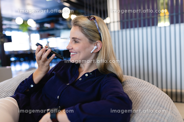 Side view of a Caucasian businesswoman wearing smart clothes and earphones, working in a modern office, sitting on a bean bag and talking on the smartphone..の販売画像
