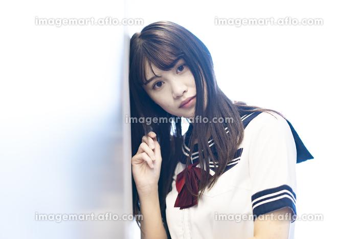 壁にもたれかかる女子高生のポートレートの販売画像