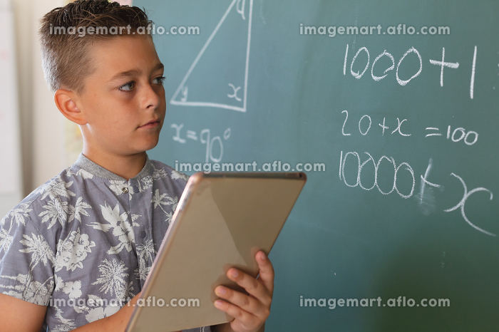 Caucasian boy standing at chalkboard in classroom and using tablet during maths lesson. childhood and education at elementary school.の販売画像