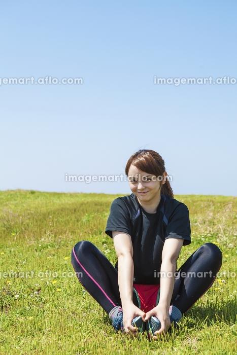 草原でストレッチをする女性の販売画像