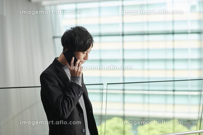 電話をかける若い日本人ビジネスマンの販売画像