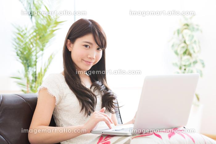 部屋でパソコンを見る女性の販売画像