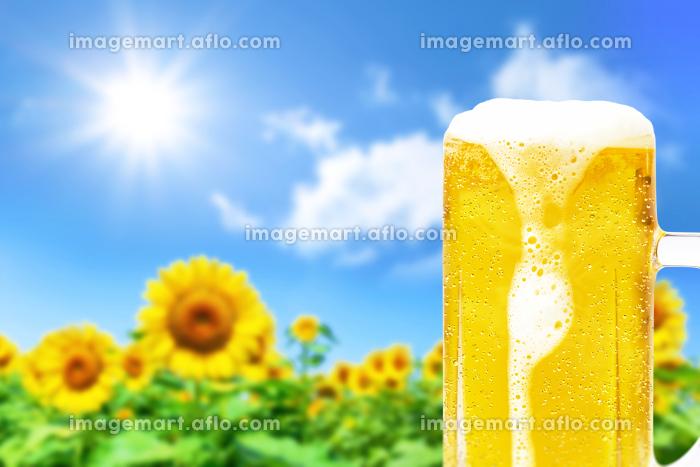 ひまわりの背景と泡が垂れた水滴のついたジョッキビールの画像の販売画像