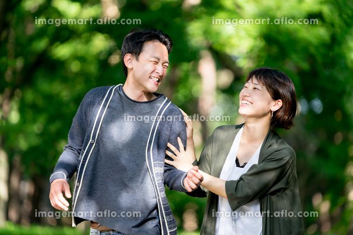 新緑の下ではしゃぐカップル(スキンシップ・デート・夫婦)の販売画像