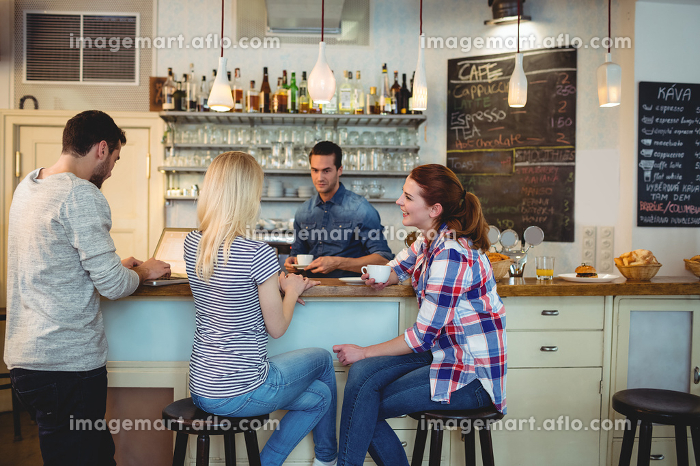Waiter looking at female customers sitting at counter in cafe