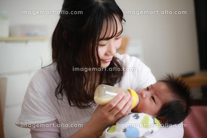 赤ちゃんにミルクを与える母親の販売画像