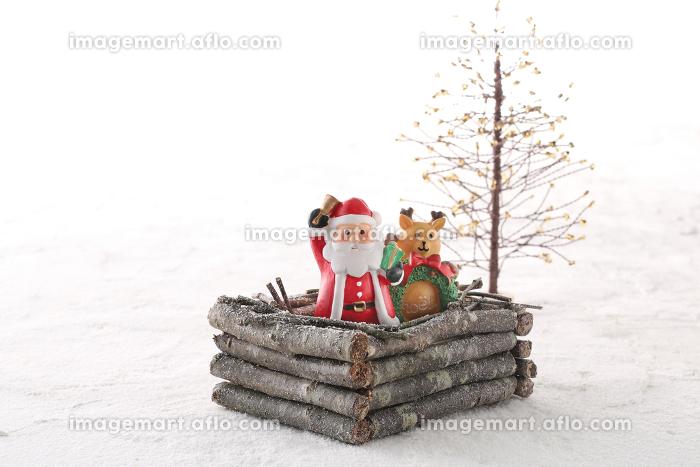 クリスマスにプレゼントを運んでくるサンタクロースと雪景色の販売画像
