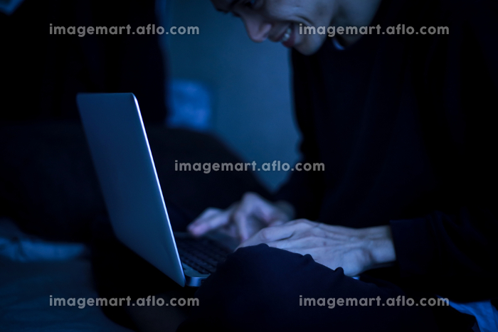 暗い中でパソコンを使う男性の販売画像