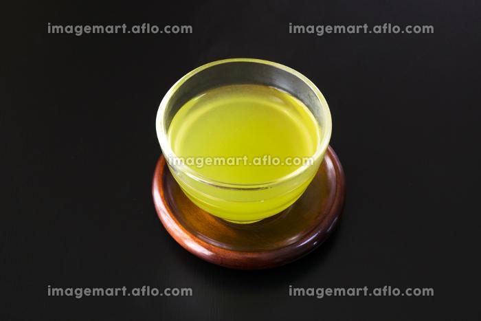 黒い背景のガラスの湯吞みに入った緑茶の販売画像