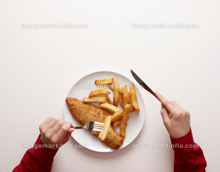 Hands by plate of fish and chipsの販売画像
