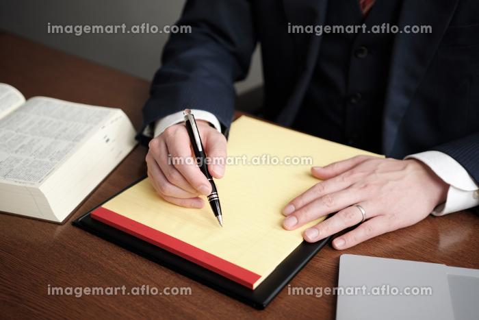 リーガルパッドにメモをする男性弁護士の手元の販売画像