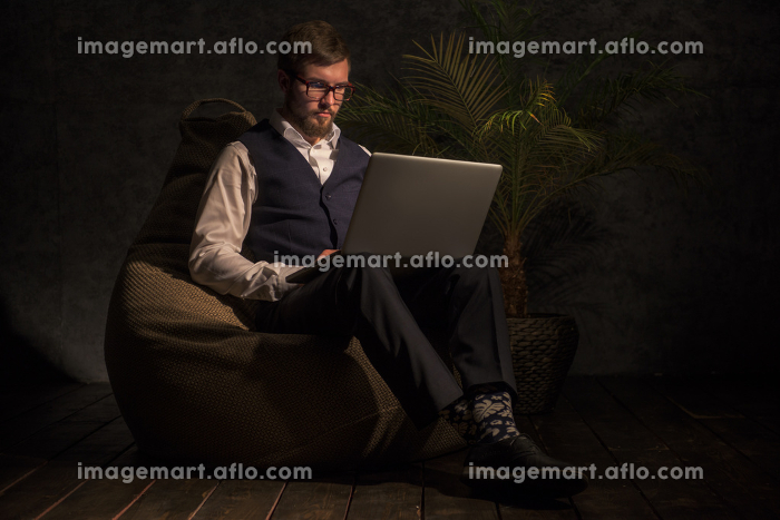 Business man Working on Laptop at home or office while sitting on beanbagの販売画像