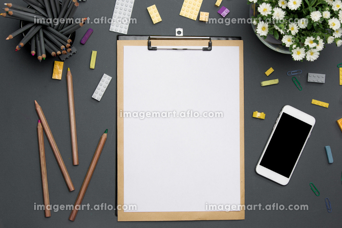 Office desk table with pencils, supplies, phone and flowersの販売画像
