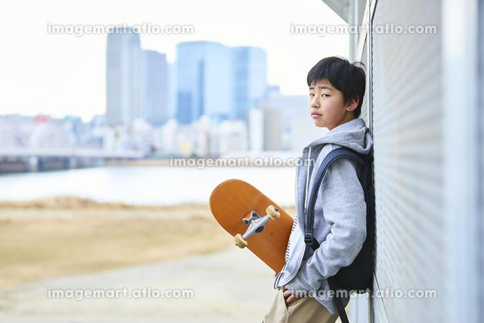スケボーを持っている日本人中学生の販売画像