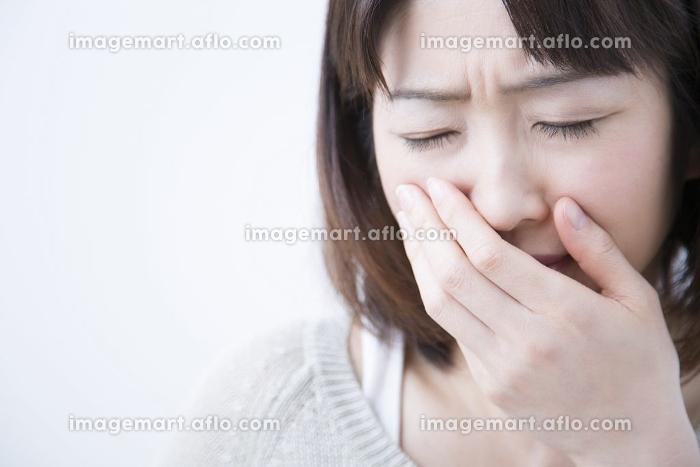 口を押えるミドル女性