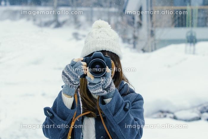 雪の中カメラを構えて撮影する日本人女性