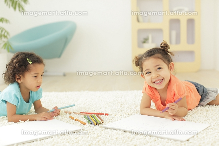白い画用紙にお絵かきをする女の子たちの販売画像