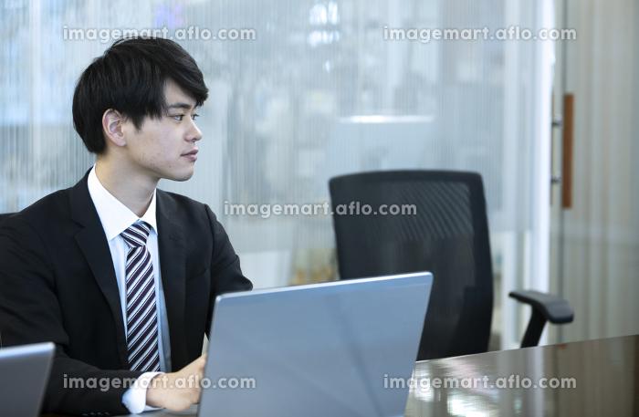 ノートパソコンを操作するビジネスマンの販売画像