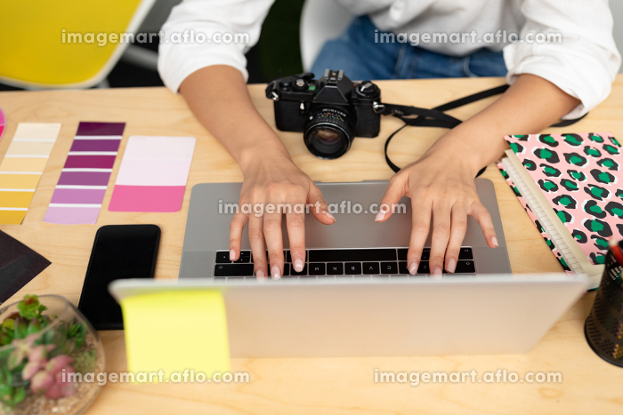 Mid section close-up of Caucasian female graphic designer using laptop at desk in office. This is a casual creative start-up business office for a diverse teamの販売画像