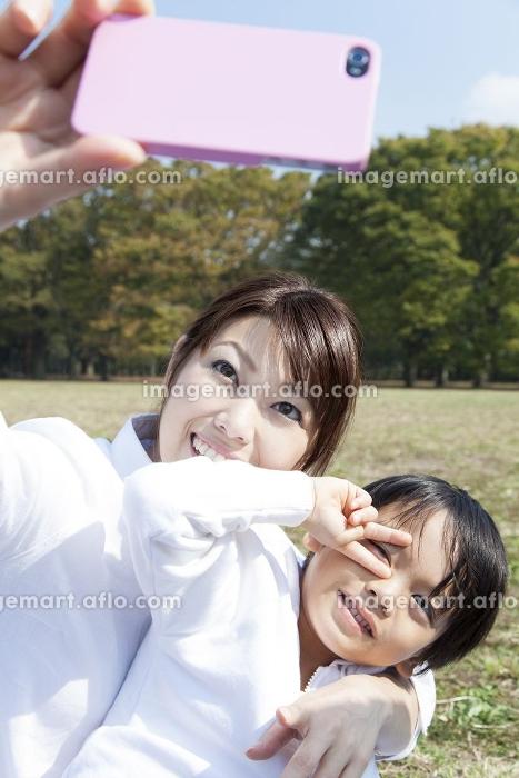 スマートフォンで写メを撮る母子の販売画像