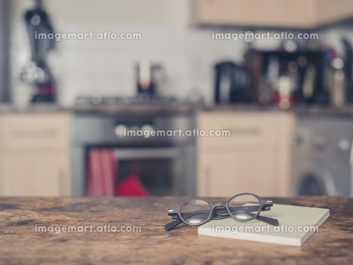 A pair of glasses and a book on a table in a kitchen.の販売画像