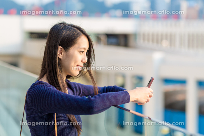 Happy woman using a smart phone in the streetの販売画像