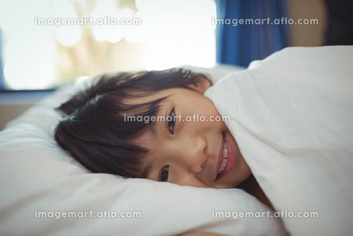 Smiling girl lying on the bed in bed roomの販売画像