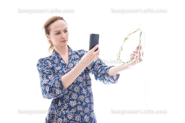 手作りの小物をオンラインマーケットに出品する女性の販売画像