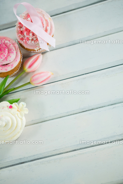 Overhead view of Breast Cancer Awareness pink ribbons on cupcakes with tulipsの販売画像
