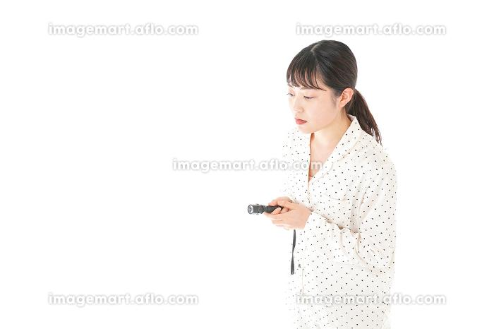 懐中電灯を使う若い女性の販売画像