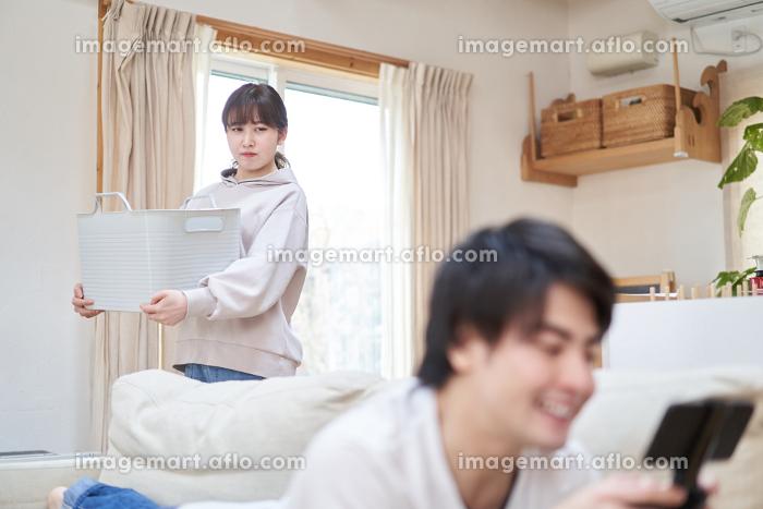 家事をする妻とゲームをするアジア人の夫の販売画像