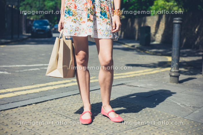 A young woman wearing a summer dress is standing in the street with a paper bagの販売画像