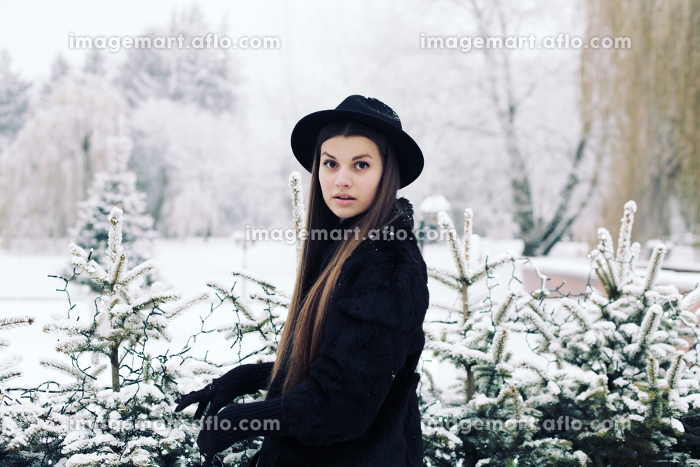 Fashion portrait of young hipster beautiful woman posing in black hat. Outdoors, lifestyle, winter.