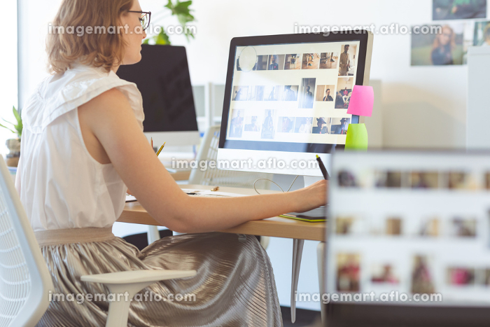 Side view of young Caucasian female graphic designer working on graphic tablet at desk in office.の販売画像