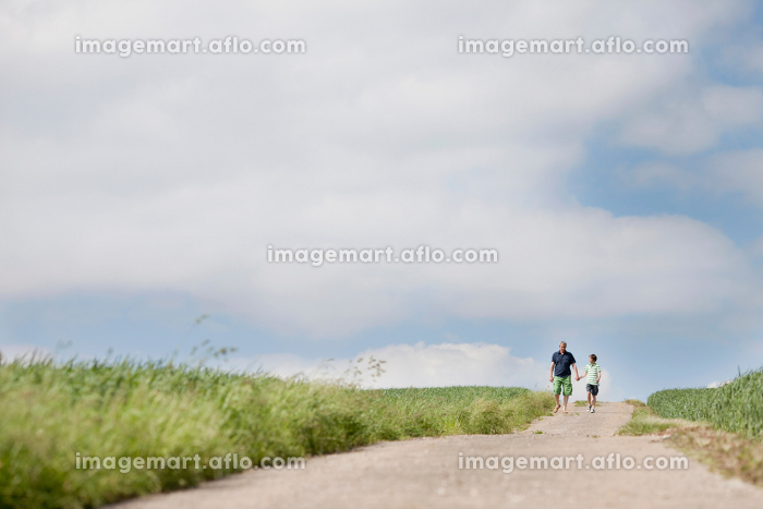 Father and son walking down a roadの販売画像