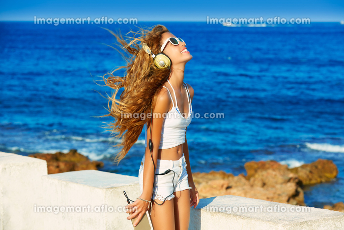 Blond kid teen girl hearing headphones music on smartphone in a beach