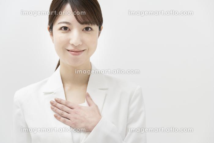 安堵のポーズを取る、白いスーツ姿の女性の販売画像
