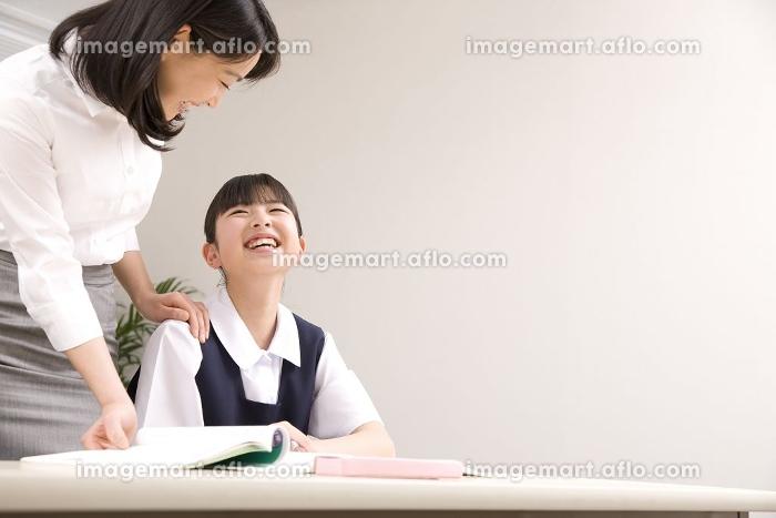 塾講師に勉強を教わる女子中学生の販売画像