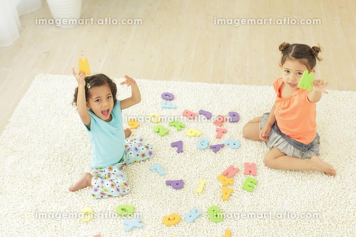 アルファベットのパズルで遊ぶ女の子たちの販売画像