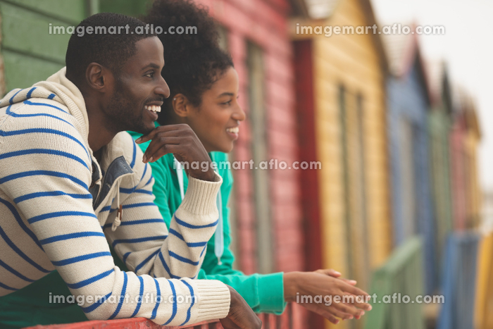 Side view of smiling Multi-ethnic couple interacting with each other while looking at the sea at beach hutの販売画像