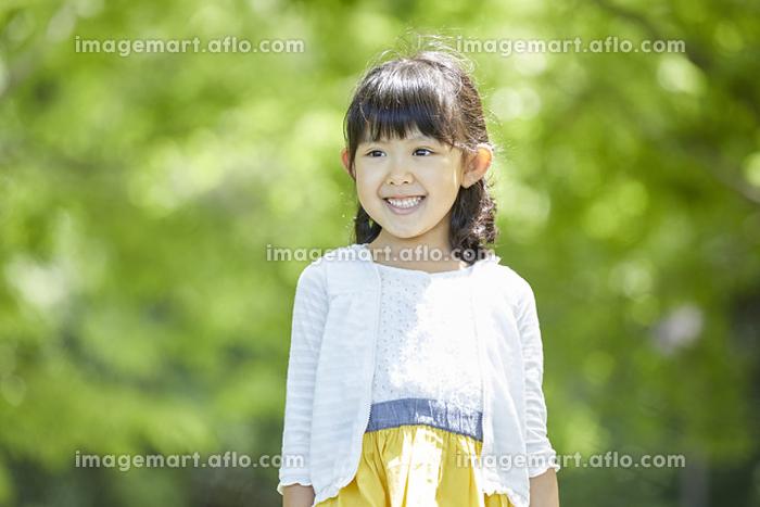 新緑の木立に立つ日本人の女の子