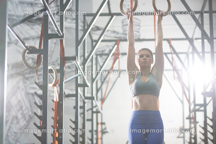 Confident woman exercising with gymnastic rings in crossfit gymの販売画像