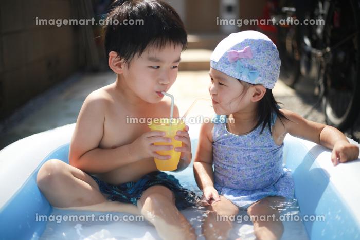 ビニールプールで仲良く飲み物を飲む子供たちの販売画像