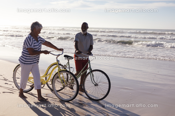 Happy senior african american couple with bicycles walking together on the beach. travel vacation retirement lifestyle conceptの販売画像