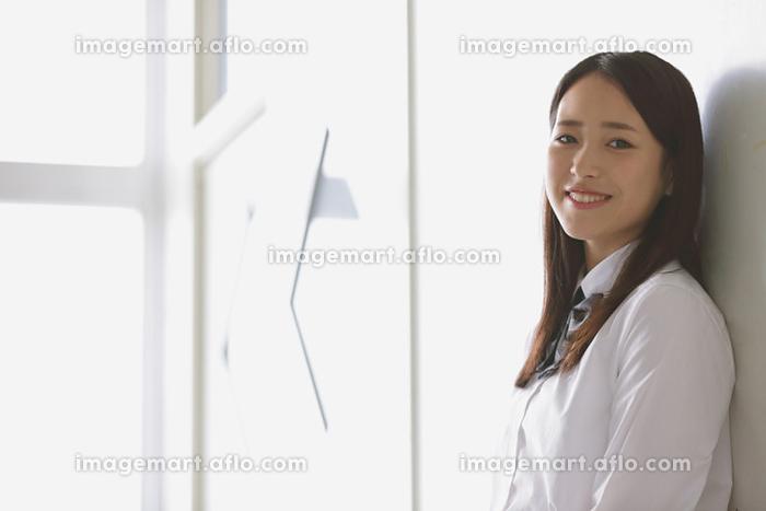 教室のドアに寄り掛かる女子高生の販売画像