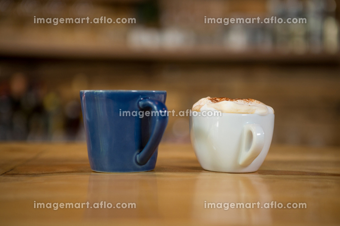 Coffee cups on wooden table in cafeの販売画像